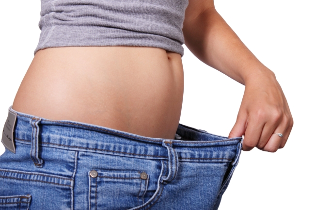 woman holding jeans away from her belly